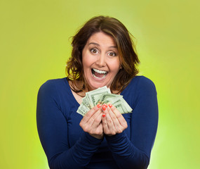 excited business woman holding money on green background
