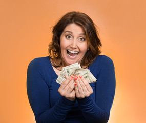 excited business woman holding money on orange background