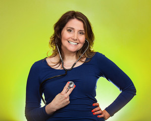 woman listening her heart with stethoscope on green background
