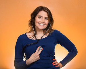woman listening her heart with stethoscope on orange background