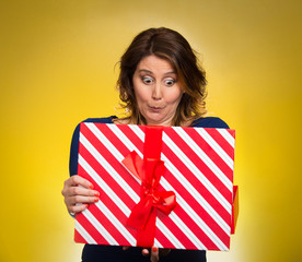 woman opening red gift box, surprised yellow background