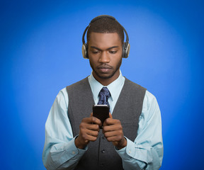 man with headphones using smartphone blue background