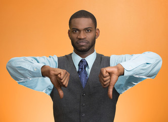 man giving thumbs down gesture isolated on orange background