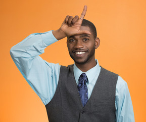 man showing loser sign on forehead isolated on orange background