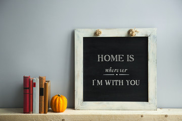 chalkboard frame on the grey wall with books and pumpkin HOME
