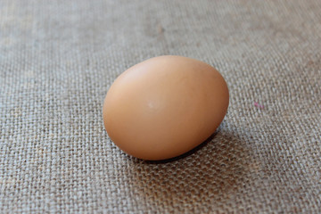 an egg of hen on the sacking background