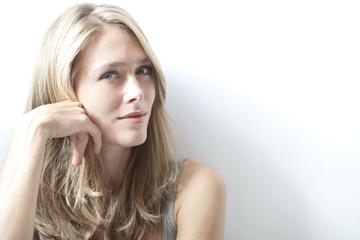 Junge blonde Frau vor weissem Hintergrund, Portrait