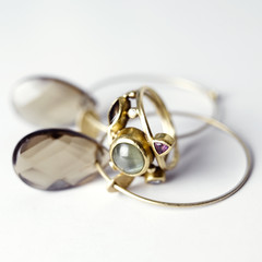 Golden ring and earrings against white background