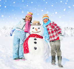 Siblings Posing Next To A Snowman