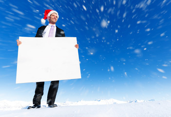Christmas Businessman Holding Blank Placard on Top of a Mountain