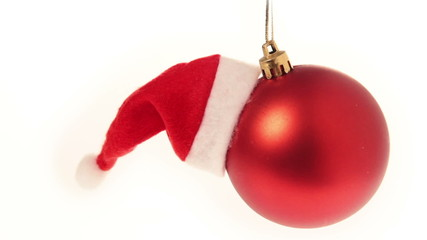 Christmas ball with santa hat hanging from the chrismtas tree.