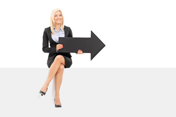 Businesswoman holding black arrow seated on panel