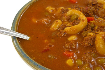 Hamburger soup in bowl with spoon close view