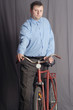 man standing near red bicycle