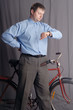 man standing near bicycle looking at watch
