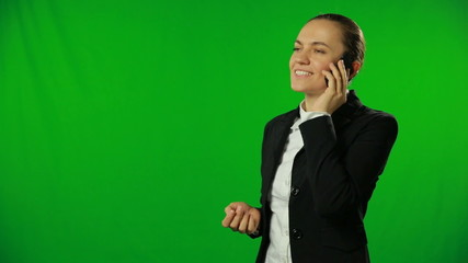 Pretty businesswoman talking on the phone, green background