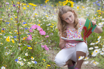 Girl looking at botany book in field of wildflowers