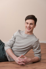young casual man sitting and smiling to the camera.