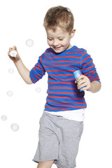 Young boy playing with bubbles, studio