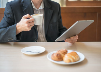 Man with tablet computer reading news at motning in cafe