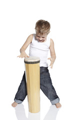 Young boy playing drum in studio