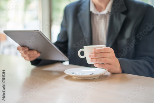 Man with tablet computer reading news at motning in cafe - 71587386