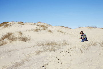 Young boy crouching on beach under blue sky