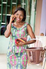 jeune femme africaine souriant au  téléphone