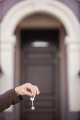 man holding keys in front of house door.