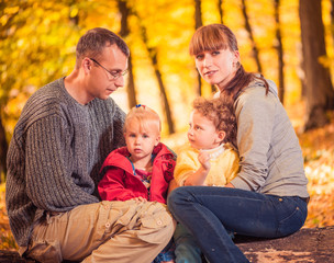 parents with two little girls at fall forest