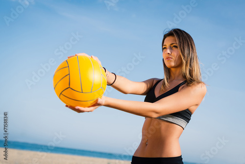 Plakat Beautiful beach volleyball female player serving ball.