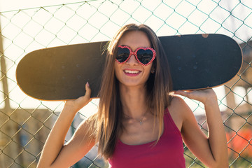 Teenager with skateboard close up portrait in the street against