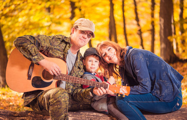 family portrait with guitar at fall forest