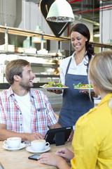 Smiling waitress serving salad plates in restaurant