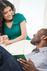 Couple in living room talking while sitting on sofa.