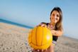 Beautiful beach volleyball female player serving ball.