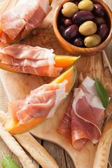 cantaloupe melon with prosciutto grissini olives. italian appeti