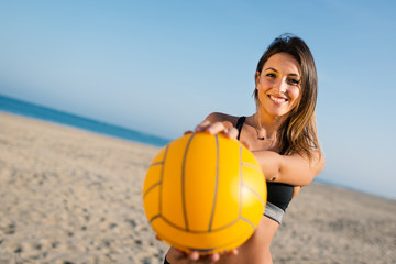 Beautiful beach volleyball female player serving ball.
