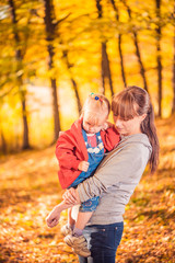 mother holding daughter in her arms at fall forest