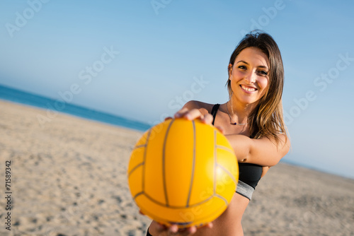 Beautiful beach volleyball female player serving ball. Poster