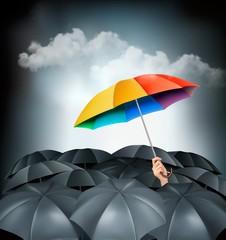 One rainbow umbrella standing out on a grey background.