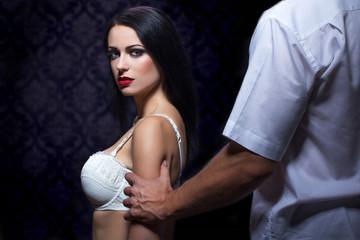 Strong man grabs woman arm at night