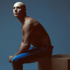 Handsome bald muscular male model in blue jeans