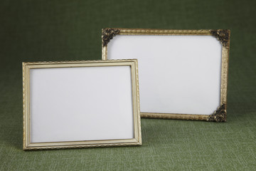 Blank picture frames against green background