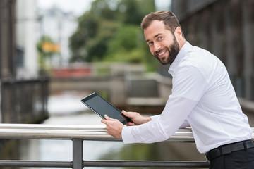 sympathischer geschäftsmann mit tablet-pc
