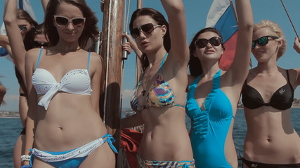 Slender models having fun, laughing and dancing on a yacht