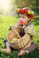 Cute boy wearing a crown of fruit with a basket of apples biting