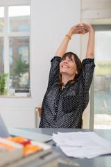 lächelnde frau im büro streckt die arme nach oben