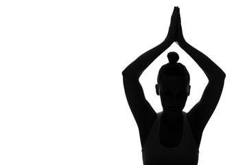 Silhouette of young woman with arms raised