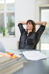 frau im büro schaut nachdenklich auf laptop